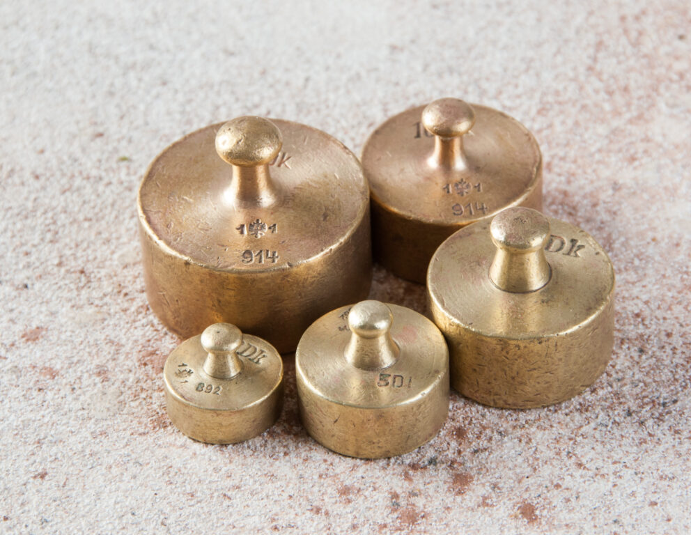 Five antique bronze weights for scales on concrete background.